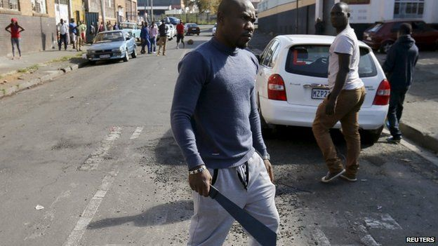 An African immigrant holds a machete before being dispersed by police officers in Johannesburg, April 17, 2015