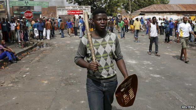 A local gestures as he holds a stick and a shield outside a hostel during anti-immigrant related violence in Johannesburg, April 17, 2015