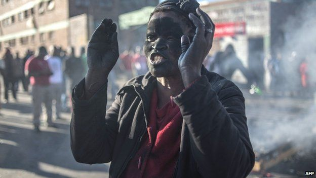 A women covered in soot gestures and shouts towards foreign nationals outside the Jeppies Hostles, in the Jeppestown area of Johannesburg, on April 17, 2015