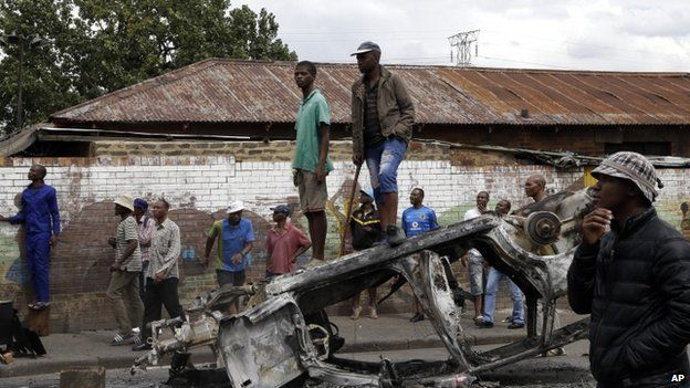 A crowd of anti-immigrant protesters stand on a burned-out car outside the Jeppe hostel in Johannesburg, South Africa, Friday, April 17, 2015