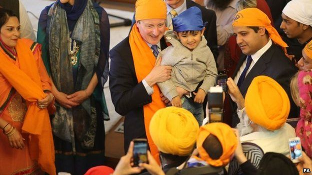 Prime Minister David Cameron holds a child on a visit to the Guru Nanak Darbar Gurdwara in Gravesend