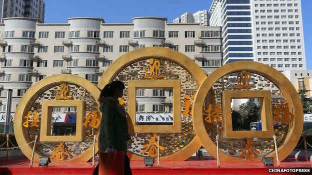 People walk past a copper coin-shaped decoration for Chinese New Year on January 20, 2014 in Zhengzhou, China.
