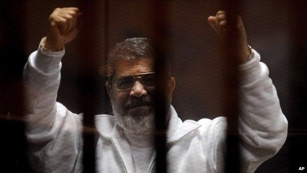 Mohammed Morsi gestures in the dock at a courtroom in Cairo, Egypt (3 March 2015)