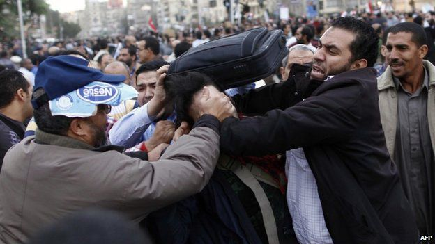 Members of the Muslim Brotherhood and supporters of Egyptian President Mohammed Morsi scuffle with an anti-Morsi protester during clashes outside the presidential palace on December 5, 2012 in Cairo