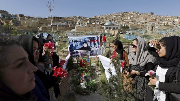 Afghan women's rights activists hold flowers at the grave of Farkhunda who was lynched by a crowd of men in central Kabul on March 26, 2015.