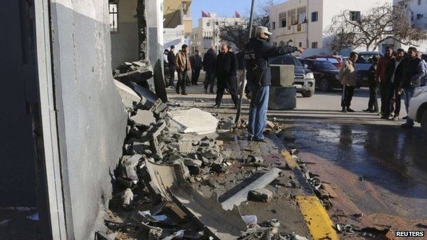 Civilians and security personnel stand at the scene of an explosion - which Islamic State said it carried out - at a police station in Tripoli (12 March 2015)