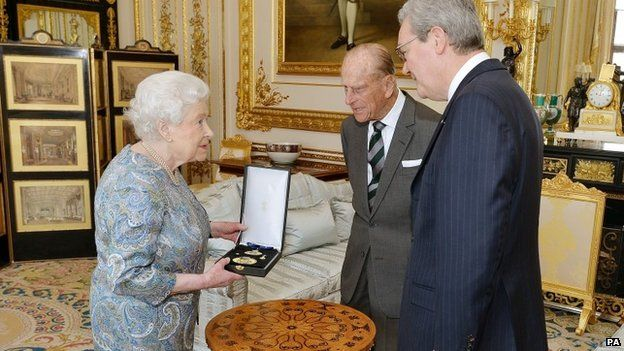 Queen Elizabeth II talks with the Australian High Commissioner, Alexander Downer (right) as she prepares to present the Duke of Edinburgh, with the Insignia of a Knight of the Order of Australia
