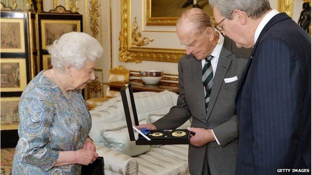 Queen Elizabeth II presents Prince Philip with the Insignia of a Knight of the Order of Australia with Australian High Commissioner Alexander Downer