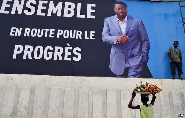 Passers-by walk past a poster of Togolese President Faure Gnassingbe in the capital, Lome.