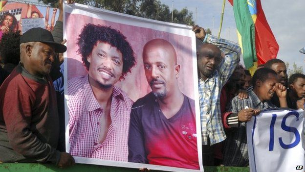 Protesters hold a banner showing two of the people killed by IS in Ethiopia