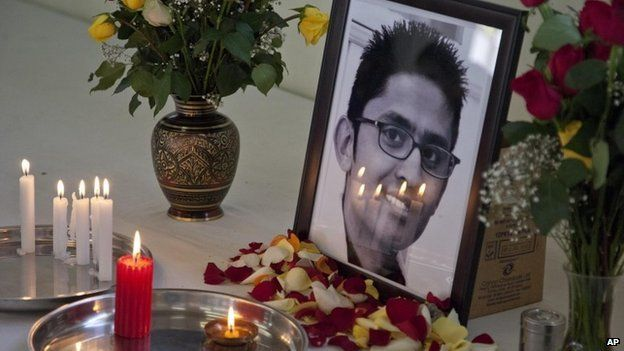 Candles reflect on the photo of late 24-year old Rajan Lalitkumar Solanki, during a prayers ceremony at Arya Samaj Temple in Nairobi, Kenya, Sunday, 29 September 2013