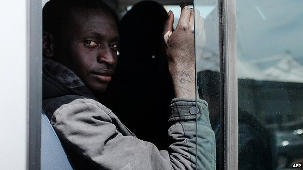 A rescued migrant with a number on his right arm, sits on bus after disembark off the Italian Guardia di Finanza vessel Denaro at the Sicilian harbour of Catania on 23 April 2015