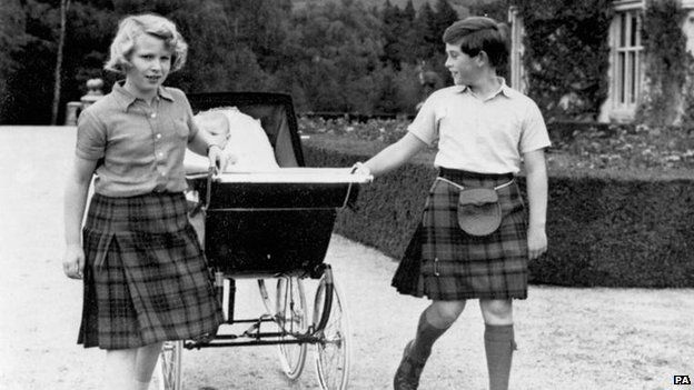 Prince Charles and Princess Anne pull a pram containing their baby brother Prince Andrew