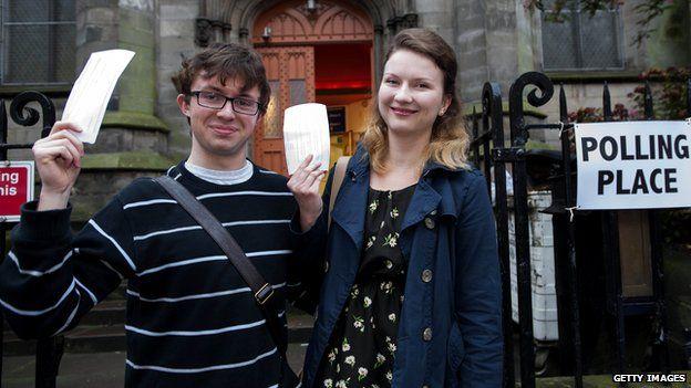 Couple hold up voting slips outside Edinburgh polling station