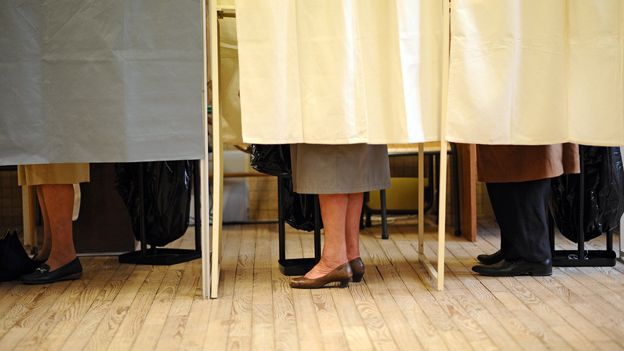 People behind curtained polling booths in France