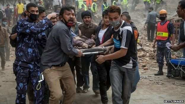 Emergency rescue workers carry a quake victim on a stretcher after Dharara tower collapsed in Kathmandu (25 April 2015)