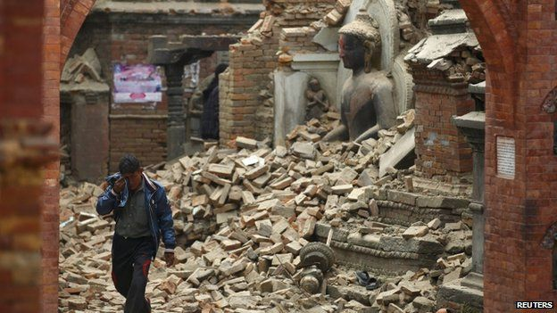 A man cries as he walks on the street while passing by a damaged statue of Lord Buddha in Bhaktapur - 26 April