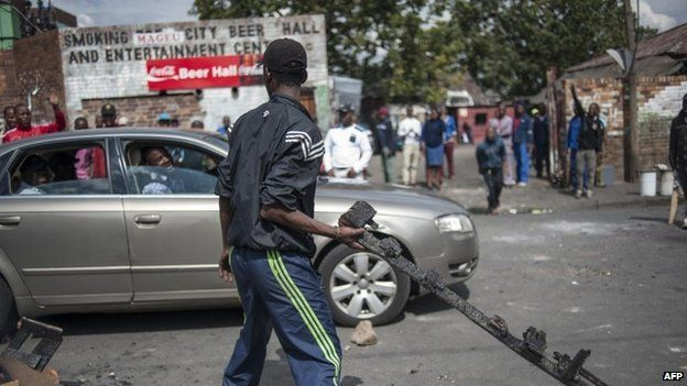 A man holds a piece of burnt wood as Zulu protesters demonstrate against foreign nationals in front of their hostel in the Jeppestown district of Johannesburg on 17 April 2015