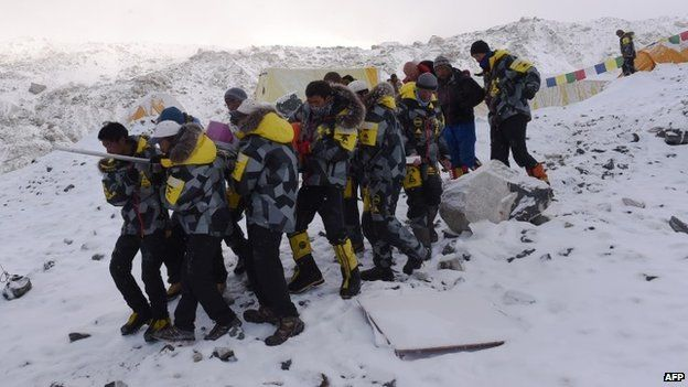 An injured person is carried by rescue members to be airlifted by rescue helicopter at Everest Base Camp (26 April 2015)