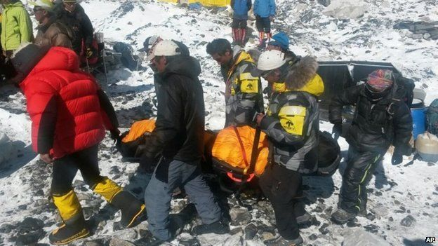 In this Sunday, April 26, 2015 photo, a person critically injured in an avalanche is carried on a stretcher to be evacuated out of Everest Base Camp, Nepal.