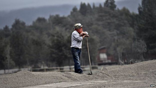 A man rests after cleaning his house affected by the Calbuco volcano eruption in Ensenada on 26 April, 2015