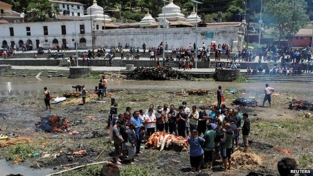 People pray before cremating a body in Kathmandu, Nepal, after the massive earthquake, 27 April 2015