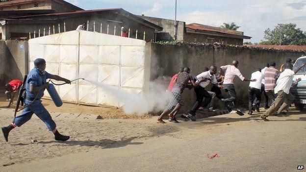 A Burundian riot policeman sprays tear gas on opposition protesters in the capital Bujumbura, Burundi Monday, April 27, 2015