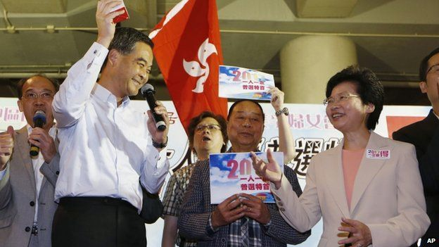 Hong Kong Chief Executive Leung Chun-ying, left, gives a gift to Chief Secretary Carrie Lam, right, during a rally to support the government's political reform proposal in Hong Kong