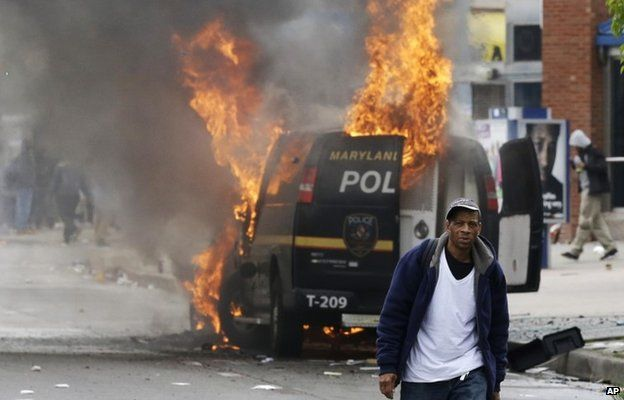 A man walks past a burning police vehicle