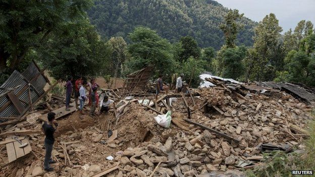 Villagers gather near a damaged house where three were killed by the earthquake at Jharibar Village, in Gorkha district close to the epicentre, on 28 April 2015