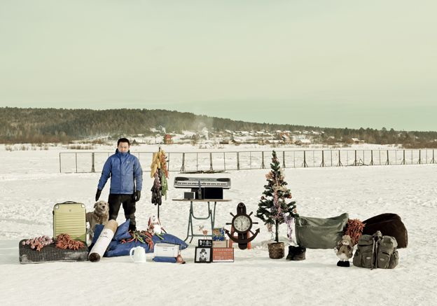 Wang Jafeng standing in the snow with his possessions