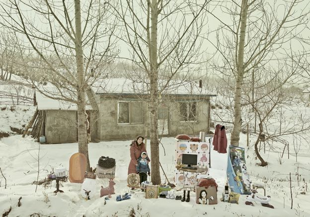 Liu Chunxiao and her son standing in the snow with their possessions