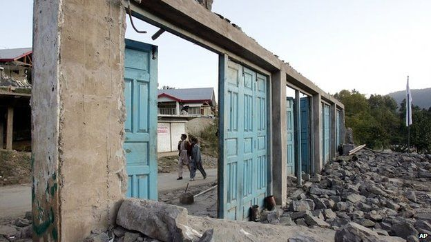 Kashmiris walk past the remains of shops destroyed by an earthquake in Pakistan on 8 October 2005