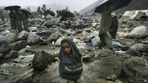 A Pakistani earthquake survivor shivers in the rain at a refugee camp in Balakot, Pakistan Saturday, Oct. 15, 2005