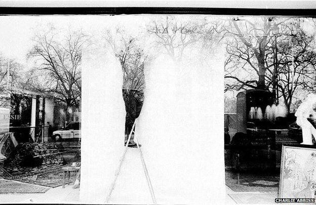 Window dresser through glass window (reflecting trees behind the camera)