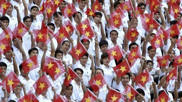 """Performers wave Vietnamese national flags during a parade celebrating the 40th anniversary of the end of the Vietnam War which is also remembered as the """"Fall of Saigon"""", in Ho Chi Minh City, Vietnam, Thursday, April 30, 2015."""