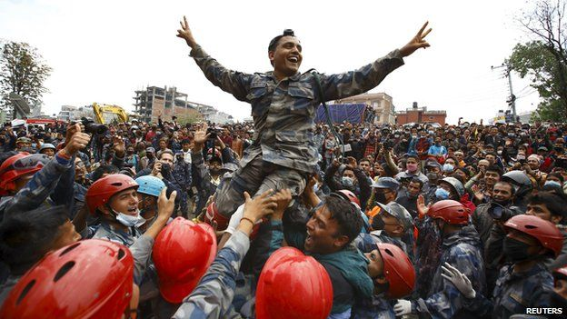 Members of the Nepalese Armed Police Force cheer after successfully rescuing earthquake survivor Pema Lama, 15, from the collapsed Hilton Hotel, in Kathmandu, Nepal (April 30, 2015)