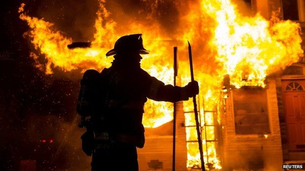 A Baltimore fire-fighter attacks a fire at a convenience store and residence during clashes after the funeral of Freddie Gray in Baltimore, Maryland in the early morning hours 28 April 2015