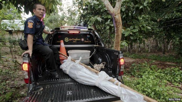 """Rescue workers transport one of the bodies found at an abandoned camp in Thailand""""s southern Songkhla province 1 May 2015."""