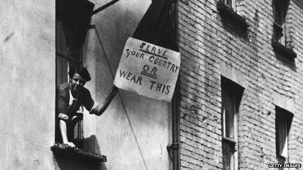 """Woman holds placard which reads: """"Serve your country or wear this"""""""