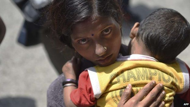 A Nepalese woman holds her sick child in her arms as she waits to be seen by medics of the Joint Disaster Relief Medical support unit of the Japanese Defence Forces at a camp in Kathmandu on May 1, 2015,