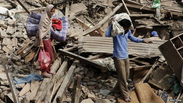 People carry their belongings as they walk on the rubble of buildings which were destroyed after last week's earthquake in Bhaktapur, Nepal, May 2, 2015.