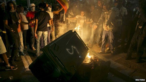 Protesters, whom are mainly Israeli Jews of Ethiopian origin, stand next to a garbage bin they set on fire at Rabin Square, Tel Aviv May 3, 2015.