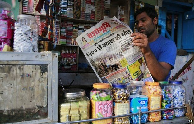 An Indian shopkeeper reads a newspaper with front-page news of Nepal earthquake in Mumbai, India, Sunday, April 26, 2015