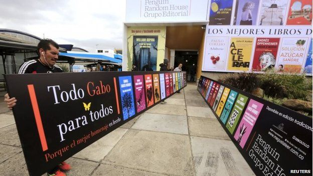 Workers carry a banner at the entrance of a library during Bogota's 28th International Book Fair, or Filbo 2015, on 22 April, 2015.