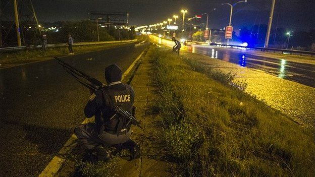 South African Policemen patrol during a standoff with looters on the National Highway in Johannesburg on 18 April 2015, as looting of foreign owned shops and xenophobic attacks escalated
