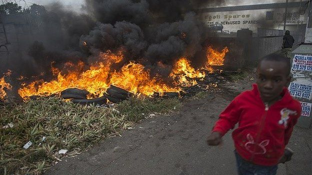 Child runs pass burning tires during the xenophic violence, on 17 April 2015 in Jeppestown area of central Johannesburg