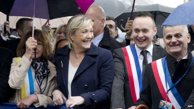 """The president of French far-right party Front National (FN) Marine Le Pen (C) holds a banner as she marches during the party""""s annual rally in honour of Jeanne d""""Arc (Joan of Arc) on 1 May 2015 in Paris."""