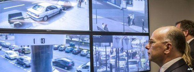 French Interior Bernard Cazeneuve looks at a surveillance screen in Calais (04 May 2015)