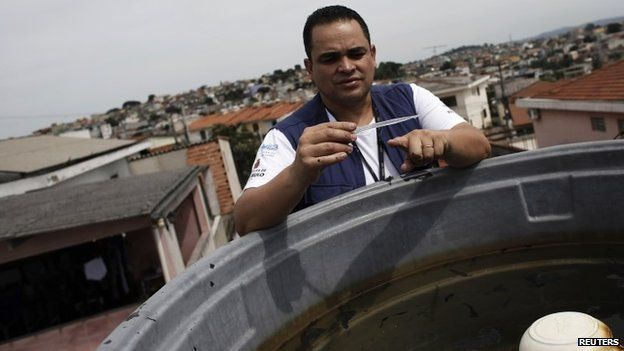 A national health official checks a water tank for mosquitoes during a house inspection
